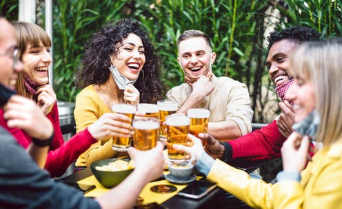 Young people toasting beer wearing open face mask
