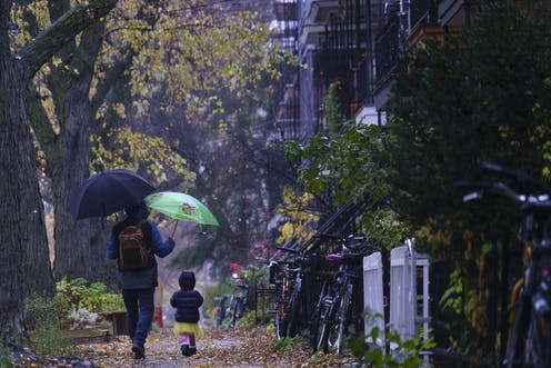 A man and child walk in the rain