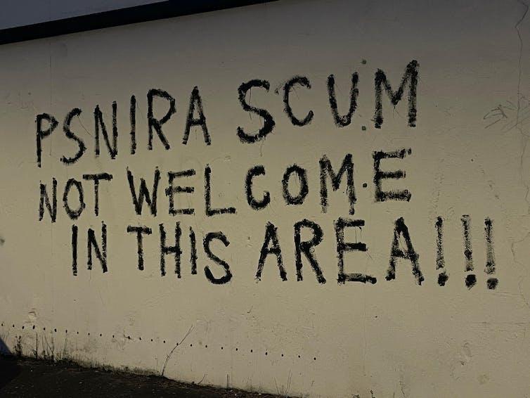 Graffiti in Belfast reading 'PSNIRA scum not welcome in this area'.