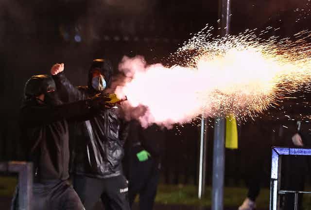 A young man shoots a firework during unrest in Belfast.