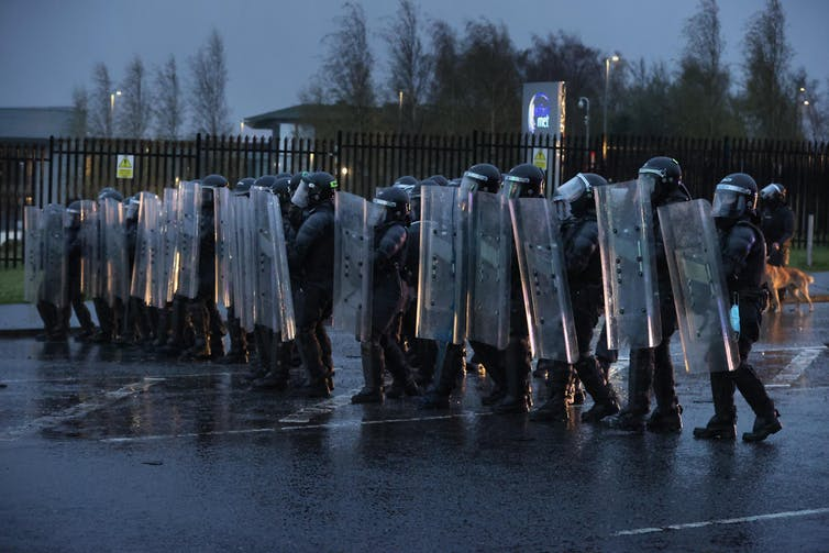 A line of riot police with shields.
