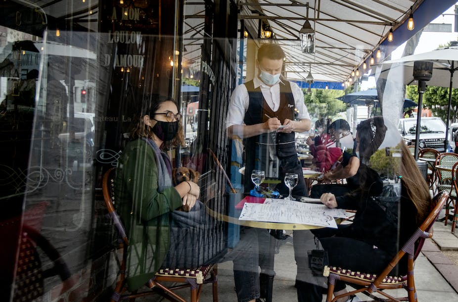 Waiter  takes food orders from customers behind a plexiglass at Figaro Bistro in Los Angeles County.