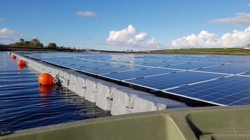 Floating solar panels mounted on plastic floats on a lake, with orange marker buoys.