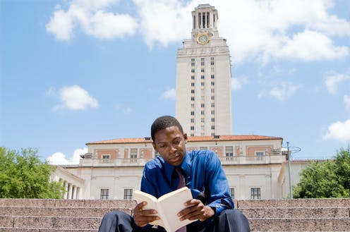 A Black college student reads a book on the steps of a college campus.