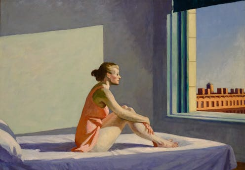 A woman sits on a bed and stares out a window.