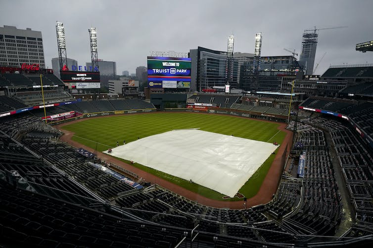 Rain falls onto Truist Park in Atlanta Georgia, where the Braves play baseball, as a tarp covers the infield