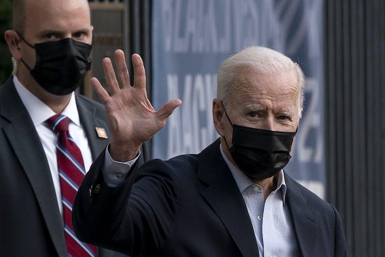 Joe Biden waves and wears a black mask