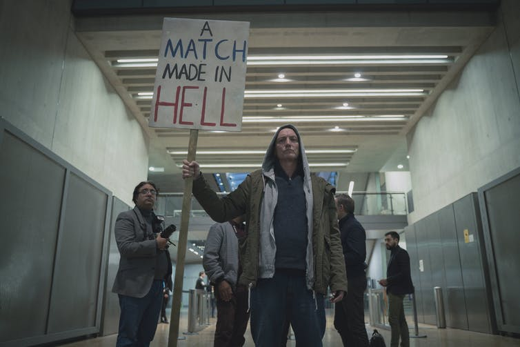 A man holds a sign: A Match Made In Hell
