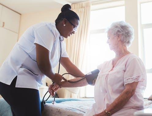 Female care worker check elderly woman's blood pressure.