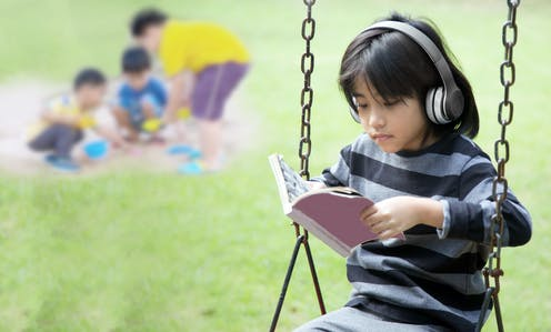A girl wearing headphones on a swing in front of three children playing