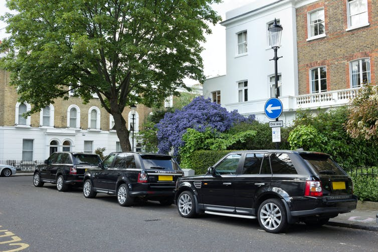 Three large, black SUVs parked in an affluent London street.