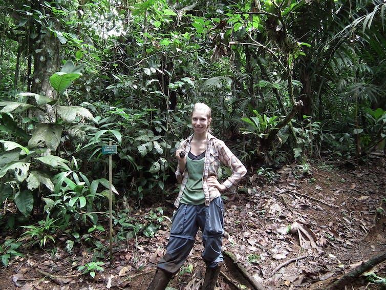Mujer de pie en medio de una selva tropical.