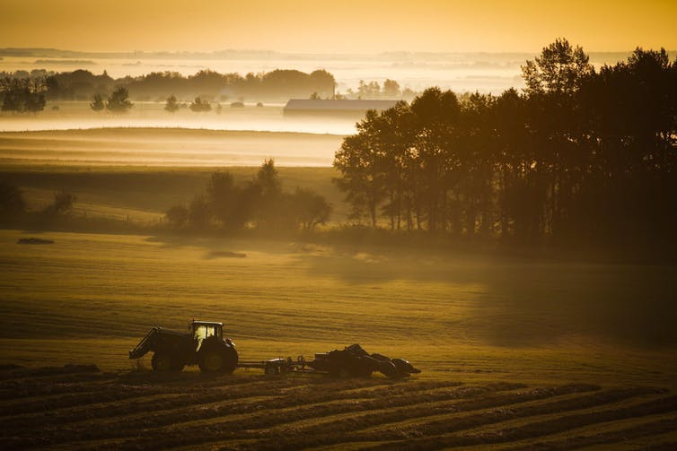 A farm tractor and baler sit in a hay field amid a misty sunrise.