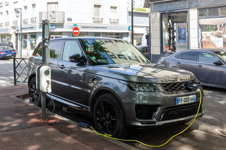A Land Rover being charged on a Paris street.
