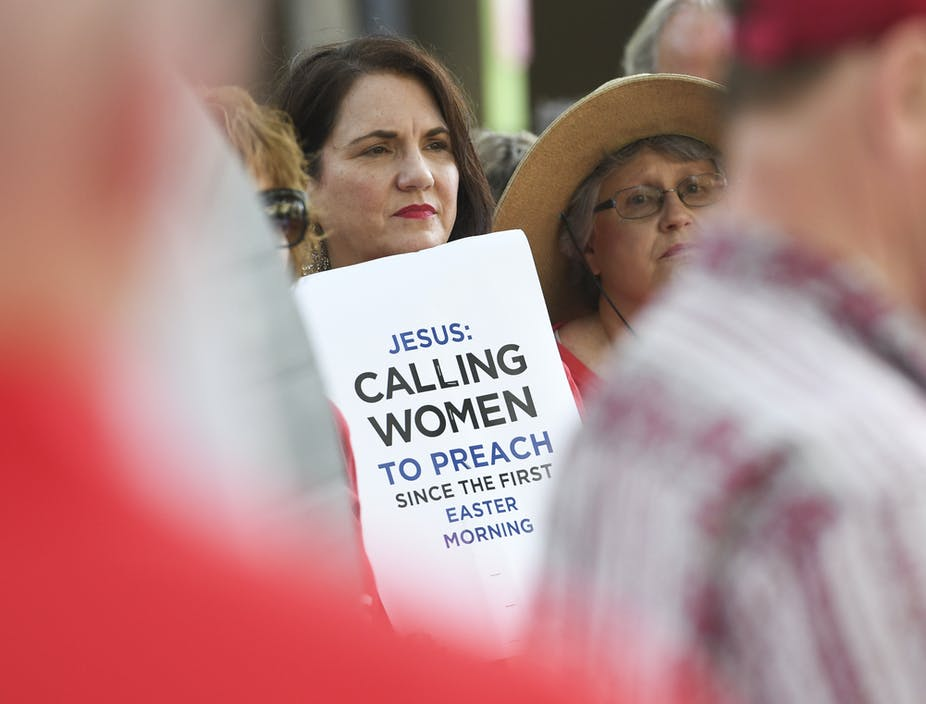 A woman holds a placard outside the Southern Baptist Convention's annual meeting in Birmingham, Alabama
