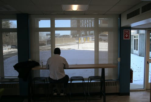 A college student sits alone, looking out onto an empty campus.