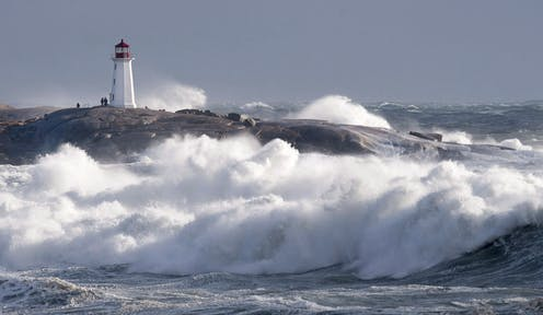 High surf and big waves with the Peggy's Cove lighthouse in the background.