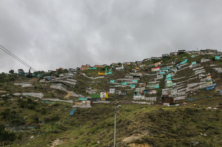 A green hillside with shacks on it