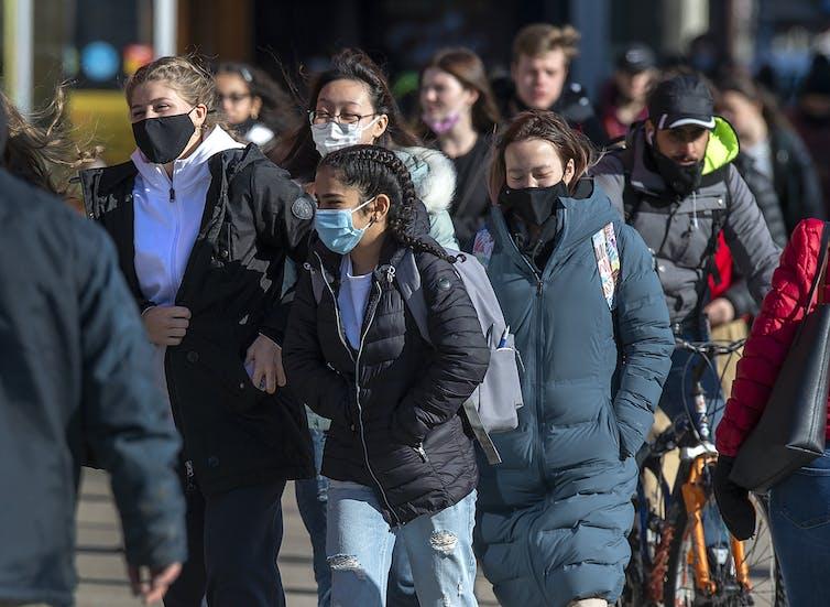 Pedestrians in face masks walk along a city street.