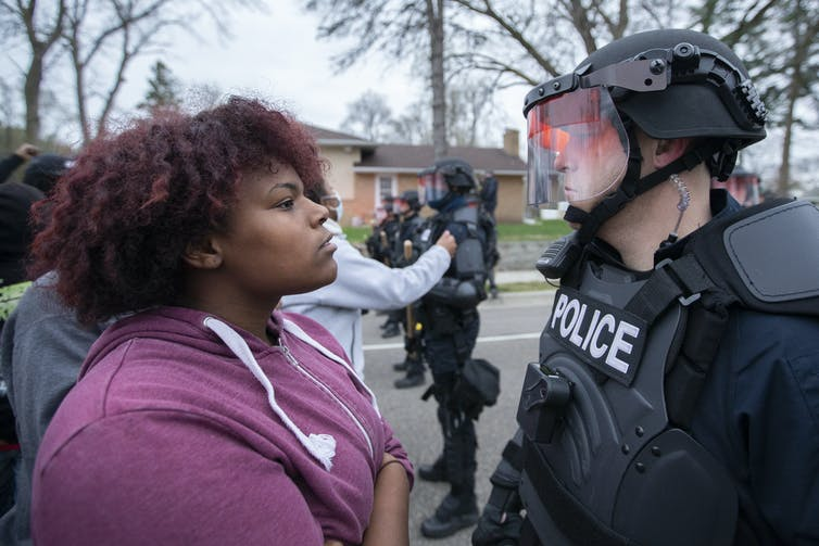 A protester stares down a police officer during a protest in Brooklyn Center, Minnesota.