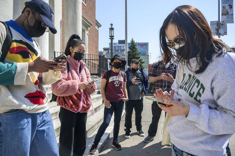 Group of people look at their phones