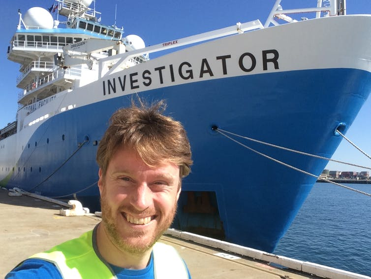 The author smiles in front of a blue and white ship, with 'Investigator' written on the side.