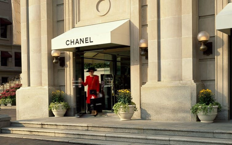 A woman in a red suit leaves Chanel.