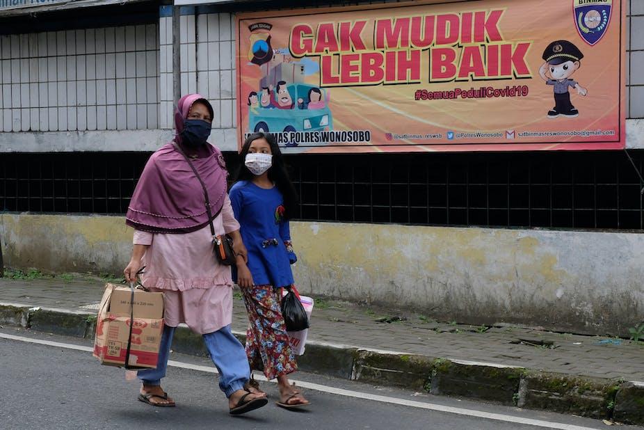 Warga berjalan di samping spanduk larangan mudik di kompleks pasar Induk Wonosobo, Jawa Tengah.