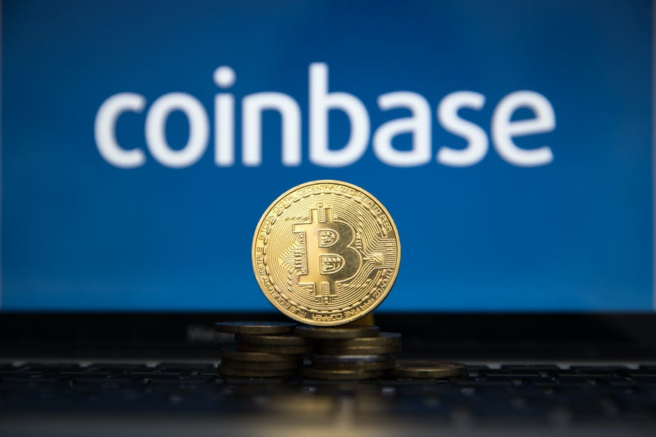 A mocked up gold bitcoin in front of the Coinbase logo