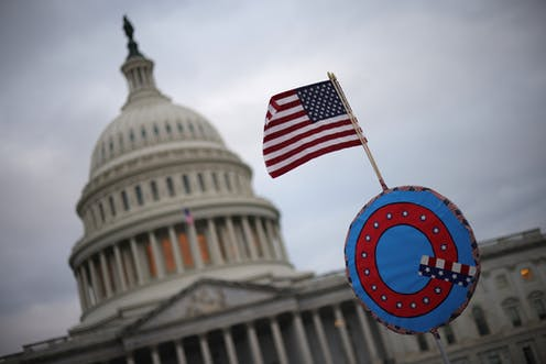 A U.S. flag adorned with a QAnon symbol flies near the U.S. Capitol.