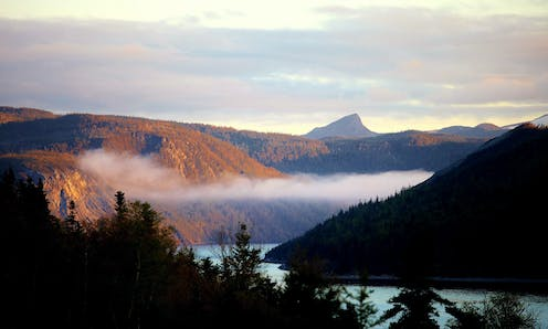 Low clouds hang in fjord as the sun reflect on the surrounding hills.