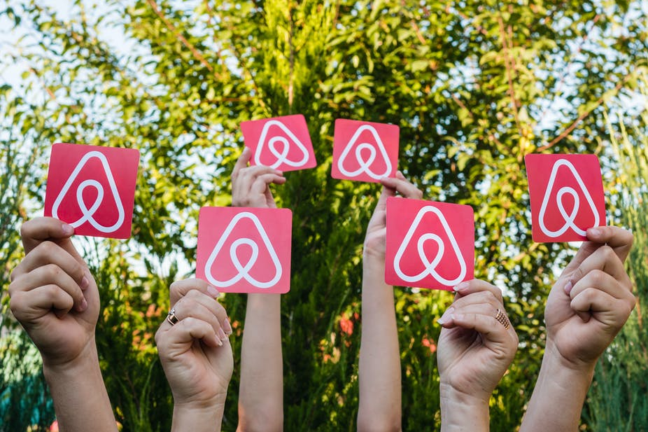 Six hands holding up Airbnb logos