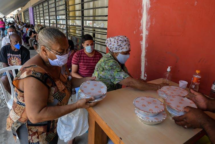 Moradores recebem refeições em um refeitório em São Paulo.