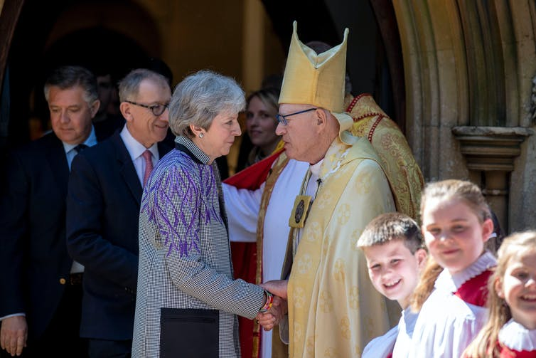 Theresa May shaking hands with an Anglican priest.