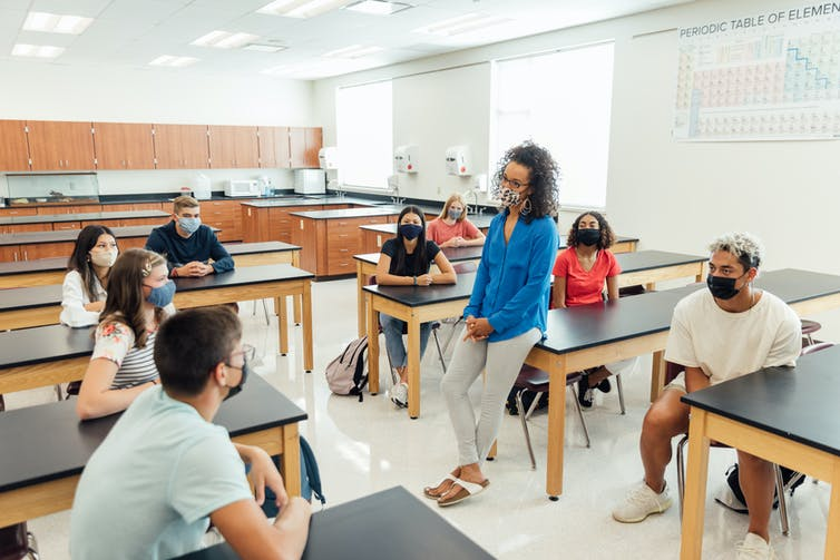 Students and their teacher sit around desks engaging themselves in a class discussion.