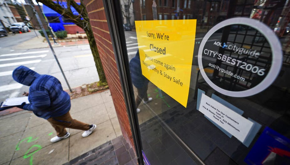 """Person in winter clothing walking down a street in Pittsburgh, Pennsylvania, past a cafe with a sign reading, """"Sorry, we're closed. Please come again. Keep healthy and stay safe."""""""