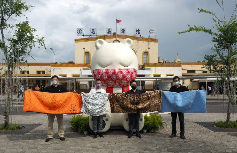 Four people holding up giant face masks stand in front of a statue of a sleeping bear.