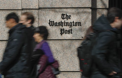 People walk in front of the Washington Post buidling
