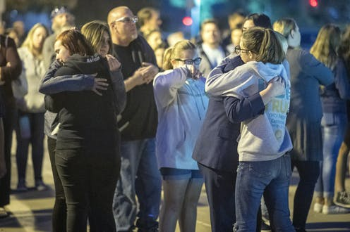 A group of children hug each other during a vigil.