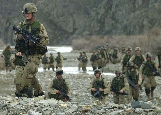 US troops carrying guns walking through a stream and on rocky ground in Afghanistan.