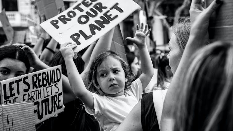 Young girl holds sign at climate protest