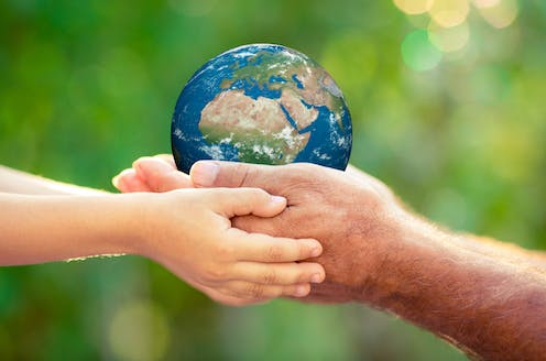 Man and child's hands holding Earth