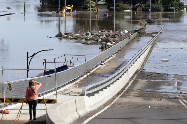 A woman looks at a bridge partially submerged in water