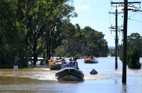 People in inflatable boats sail down a street