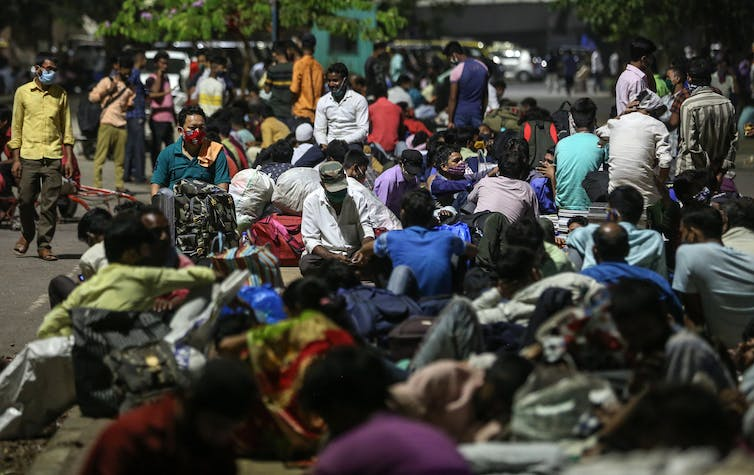 Migrant workers wait for trains in Mumbai.