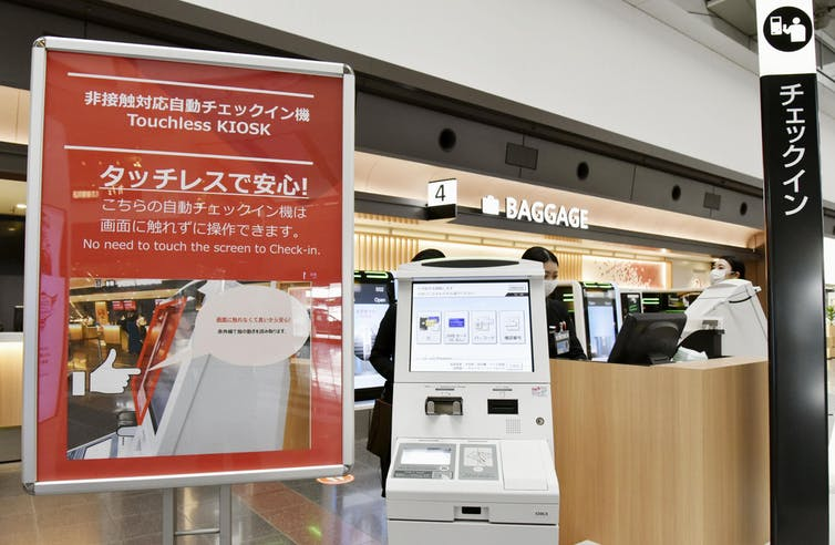 New self-service check-in machines introduced by Japan Airlines at Tokyo's Haneda airport enable passengers to complete the procedure without touching the screen.