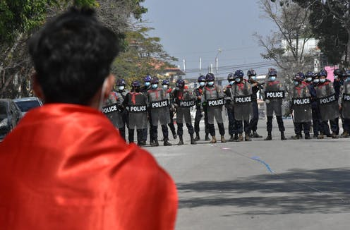 A protester watches as a line of police officers assembles wearing riot gear.