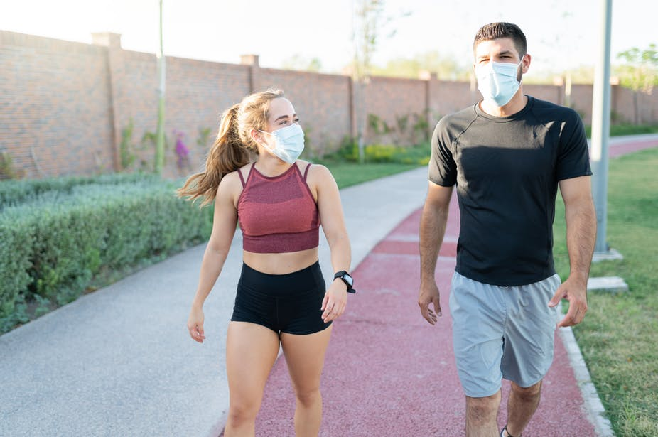 A young woman and young man walk outside in activewear while wearing face masks.