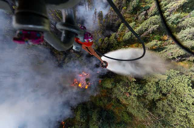 View of a forest fire looking straight down from a military helicopter dropping water.