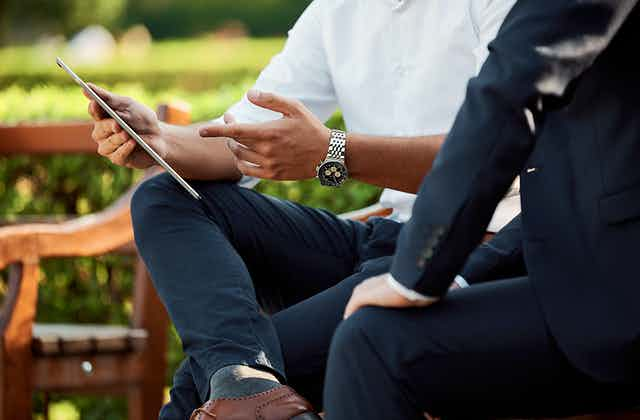 A man with rolled up shirt sleeves points to a tablet as a man in a suit sits next to him.